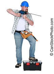 Tradesman holding a drill with a long bit