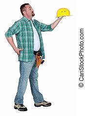 Tradesman holding a hard hat