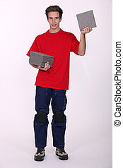 Tradesman holding a stack of tiles
