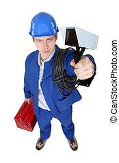 Tradesman holding a surveillance camera