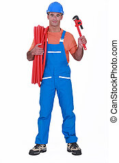 Tradesman holding corrugated tubing and a pipe wrench