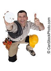 Tradesman holding up a smoke detector