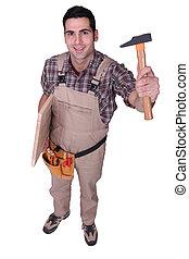 Tradesman holding up a tool
