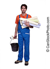 Tradesman holding wallpaper rolls