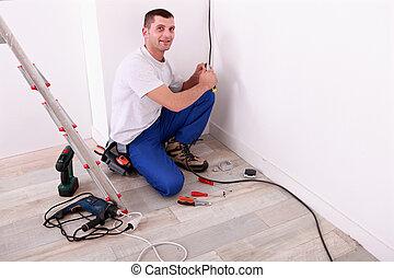 Tradesman installing electrical wiring