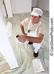 Tradesman painting a column