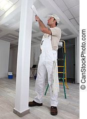 Tradesman painting a column