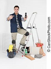 tradesman, posar, com, seu, materiais edifício, e, apontar, seu, telefone móvel