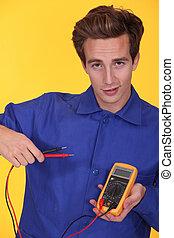 Tradesman posing with a multitester