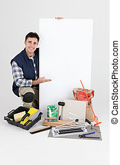 Tradesman posing with his tools and a blank sign