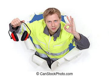 Tradesman promoting the use of earmuffs
