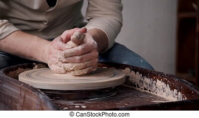 Tradesman sculpts pottery on spinning potter's wheel in workshop. Tradesman sculpts pottery on spinning Potter wheel in workshop. process of making ceramic cup.