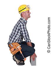 Tradesman struggling to lift a block