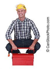 Tradesman struggling to lift his toolbox