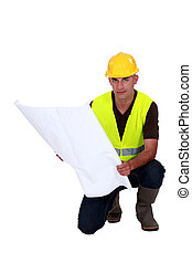 Tradesman studying a blueprint