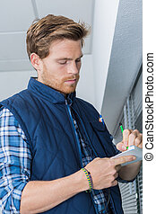 Tradesman taking notes by window