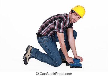 Tradesman using a sander