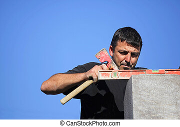 Tradesman using an axe and a bubble level