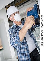 Tradesman using power tool indoors