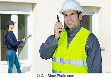 tradesman using walkie talkie stood outside a residential property