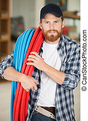 tradesman with rolls of blue and red corrugated plastic ...