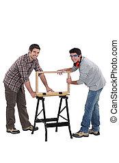 Tradesmen building a wooden frame