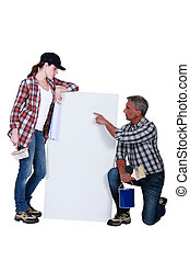 Tradespeople looking at a blank sign