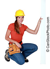 Tradeswoman holding up a sign