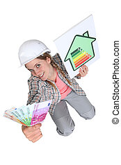 Tradeswoman holding up a wad of cash and an energy efficiency rating chart