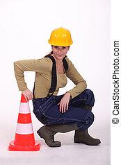 Tradeswoman kneeling next to a pylon