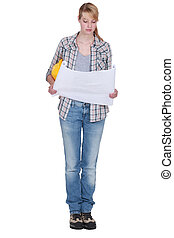 Tradeswoman looking at a blueprint