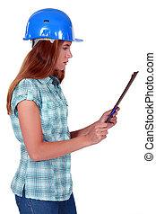 Tradeswoman looking at a clipboard