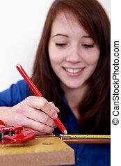 Tradeswoman measuring a copper tube