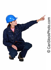 Tradeswoman pointing sideways