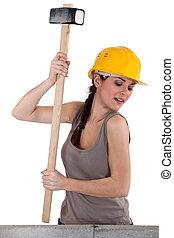 Tradeswoman using a mallet to hit stones