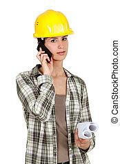 Tradeswoman using mobile phone