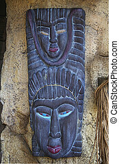 Traditional african mask hanging on grunge stone wall