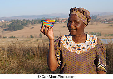 Traditional African Zulu woman selling wire baskets -...