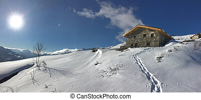 traditional alpine chalet at the top of snowy mountain under sunrise in the  sky