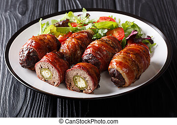 Traditional American Armadillo eggs stuffed with jalapeno and cheese wrapped in bacon served with salad close-up on a plate on the table. horizontal