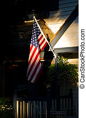 Traditional American House with Flag in Sunlight.