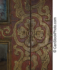 Traditional ancient Tibetan patterns on an old wooden door in a Buddhist monastery, Himalayas.