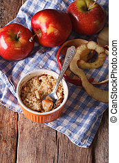 Traditional apple crumble close-up in a pot, vertical