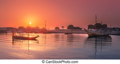 Traditional Arabic Dhow boats in Doha harbour view during...