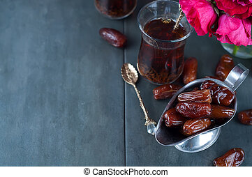 Traditional arabic tea and dry dates. roses in the...