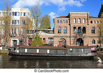 Traditional architecture and houseboat along canal, Amsterdam