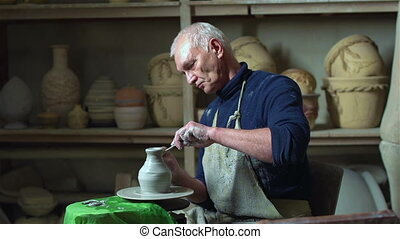 Traditional Art - Experienced master doing a clay vase on a...