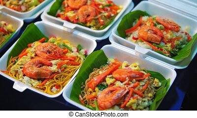 traditional Asian cuisine, street food on the night market, seafood, noodles and rice.