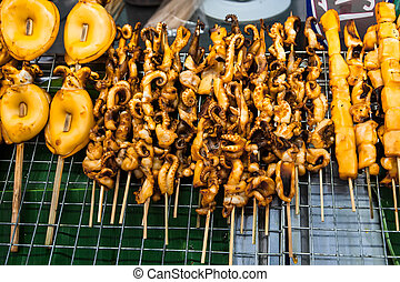Traditional asian food at market. Grilled seafood on sticks. Cal