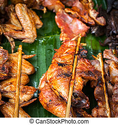 Traditional asian food at market. Delicious spicy grilled chicke